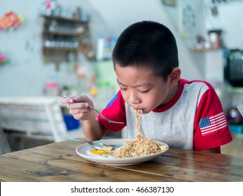 Happy Asian boy eating delicious noodle
