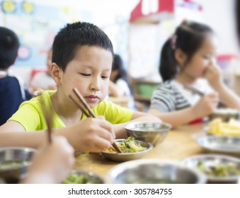Happy asian boy eating food at pre-school,China