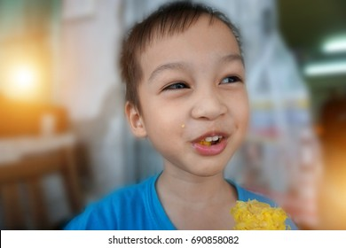 Happy asian boy was fun while eating boiled corn