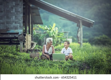 Happy Asian boy and grandmother using laptop at home, Thailand countryside area