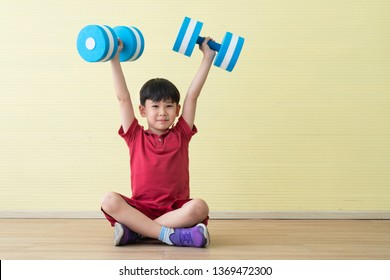 Happy Asian boy having fun, doing exercises with dumbbells, yellow background