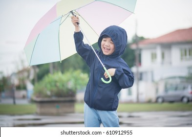 Happy asian boy holding colorful umbrella playing in the park after the rain