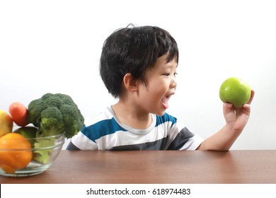 Happy Asian boy holding a green apple and a bowl of vegetables and fruits on wooden table - Childhood and healthy food concept