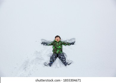 A Happy Asian Boy Making Snow Angel on a White Snow Field.