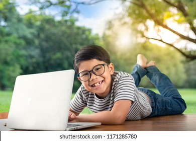 Happy Asian boy play with laptop, lying on floor at park with smiling face, kid and technology concept.
