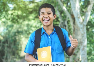 happy Asian boy student back to school hand holding books thump up and smiling at a park