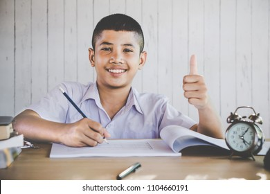 happy Asian boy student smiling at a camera studying at school writing on paper
