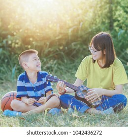 happy asian brother and sister playing ukulele and sing a song