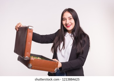Happy asian brunette woman opening retro suitcase on white background