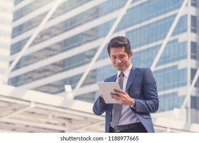 Happy Asian business man are checking their investment with a tablet.Business concept