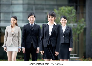 Happy Asian business team standing together with there leader.