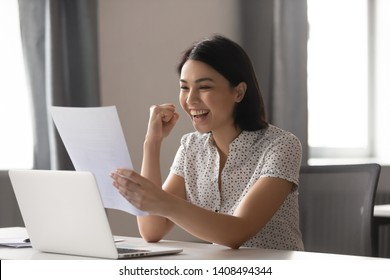 Happy asian business woman celebrate success great achievement work result look at financial report, excited japanese student winner read good news in paper letter overjoyed by admission scholarship