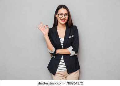Happy asian business woman in eyeglasses showing ok sign and looking at the camera over gray background