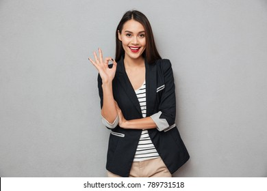 Happy asian business woman showing ok sign and looking at the camera over gray background