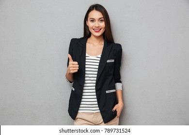 Happy asian business woman showing thumb up and looking at the camera over gray background