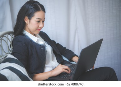 Happy asian business woman working with laptop computer in coffee shop