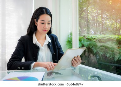 Happy asian business woman working with tablet at coffee shop