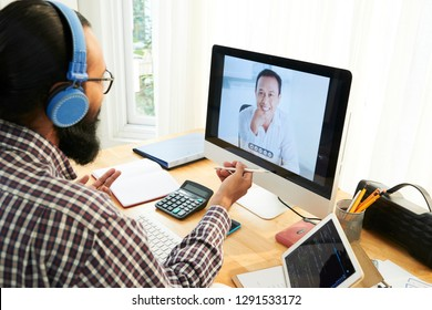Happy Asian businessman in computer screen talking online to his colleague in office sitting in front of monitor
