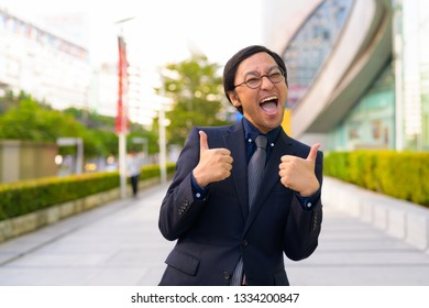 Happy Asian businessman smiling and giving thumbs up in the city outdoors