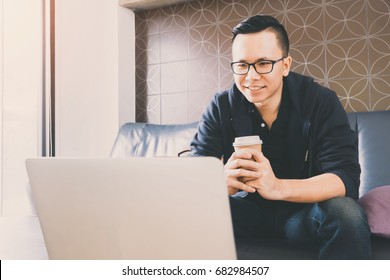 Happy asian businessman using laptop while sitting on sofa at home office background.Concept of young people working mobile devices.