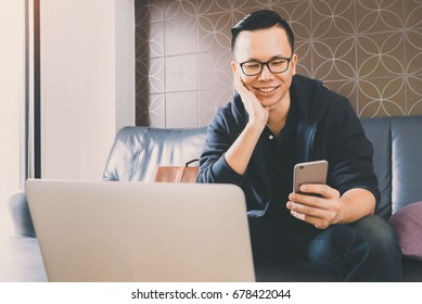 Happy asian businessman using smartphone while sitting on sofa at home office background with vintage filter.Concept of young people working mobile devices.