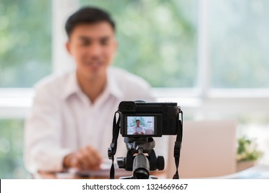 Happy Asian businessman videoblog / blogger vlogger recording online course or tutorial strategy presentation pass video for teaching live marketing sharing social media channel by mirrorless camera