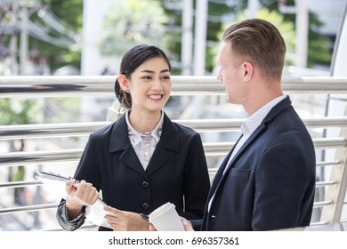 Happy Asian Businesswoman interesting for Present Project with Businessman. People Working at outdoor place. Woman Working Concept.