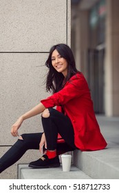 Happy asian businesswoman smiling in the city. Happy lovely and beautiful mixed race Asian Caucasian young woman in casual red suite outdoor sitting on steps of building with coffee cup. Next
