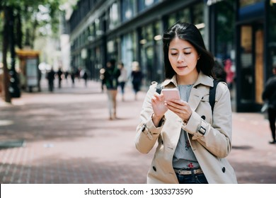 happy asian businesswoman texting message onine on cellphone standing on sidewalk going to work in morning. young office lady in casual wear using mobile phone replying email outdoor under sunshine.