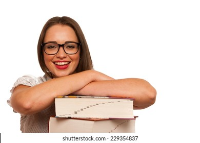 Happy asian caucasian girl leraning in study with lots of books on the table isolated