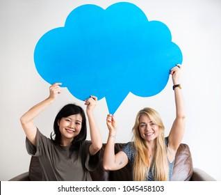 Happy Asian and Caucasian women friends holding copyspace speech bubble