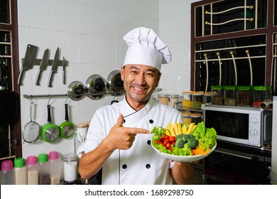 Happy asian chef showing plate with raw vegetables on the kitchen. Selective focus.