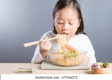 Happy Asian child age 6 years eating delicious noodle, small thai girl eating noodles with chopsticks in glass bowl with chopsticks