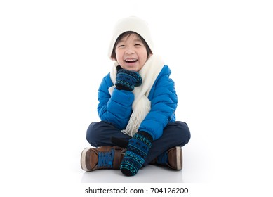 Happy asian child in  blue winter clothes sitting on white background isolated