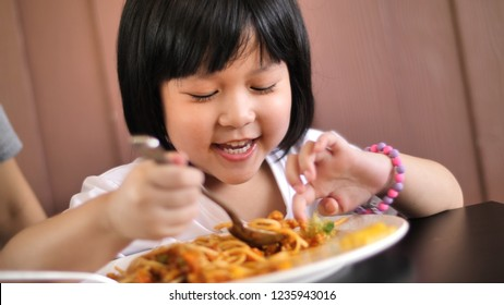 Happy Asian child eating delicious spaghetti