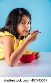 Happy Asian child eating delicious noodle, small indian girl eating noodles in red bowl, over blue background