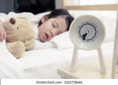 Happy asian child girl and alarm clock wake up in the morning, New family and baby healthy concept
