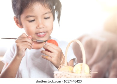 Happy asian child girl drawing and painting on easter egg prepare for easter day