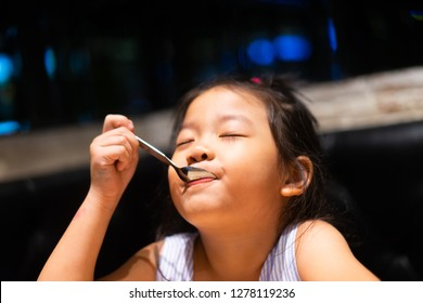 Happy asian child girl eating ice cream and  she have spoon in her mouth in restaurant.Enjoying delicious face.