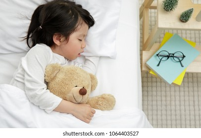 Happy asian child girl with her teddy bear sleeping in the bed, Baby healthy and preschool concept