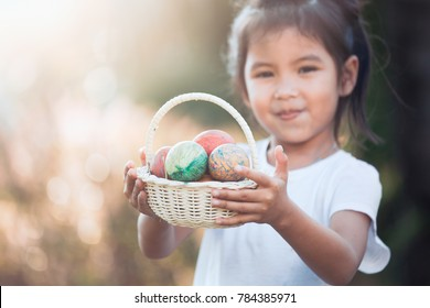 Happy asian child girl holding basket with colorful Easter eggs in outdoor