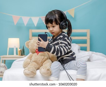 Happy asian child girl listening the music with headphone with teddy bear on the bed, technology concept for baby