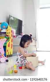 Happy Asian child girl playing with wooden blocks and having fun.