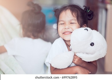 Happy asian child girl smiling and hugging her doll with love in the house in vintage color tone