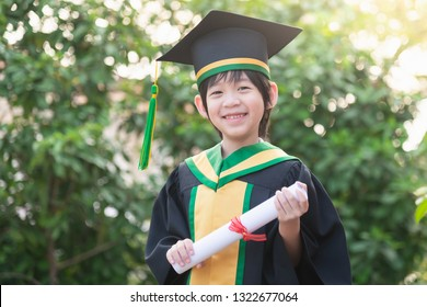 Happy Asian child in graduation gowns holding a Certificate.Graduation concept