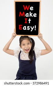 Happy asian child holding blackboard on Gray background, WE MAKE IT EASY! message on board