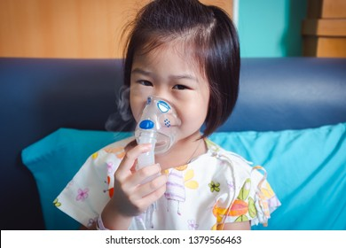 Happy asian child holds a mask vapor inhaler for treatment of asthma. Breathing through a steam nebulizer.Illness girl admitted in hospital.