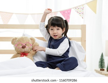 Happy asian child little girl with her teddy bear, family concept at home