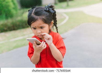 Happy Asian child little girl playing game on mobile phone in park. Concept Communication , technology