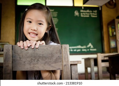 Happy Asian child in the old vintage classroom